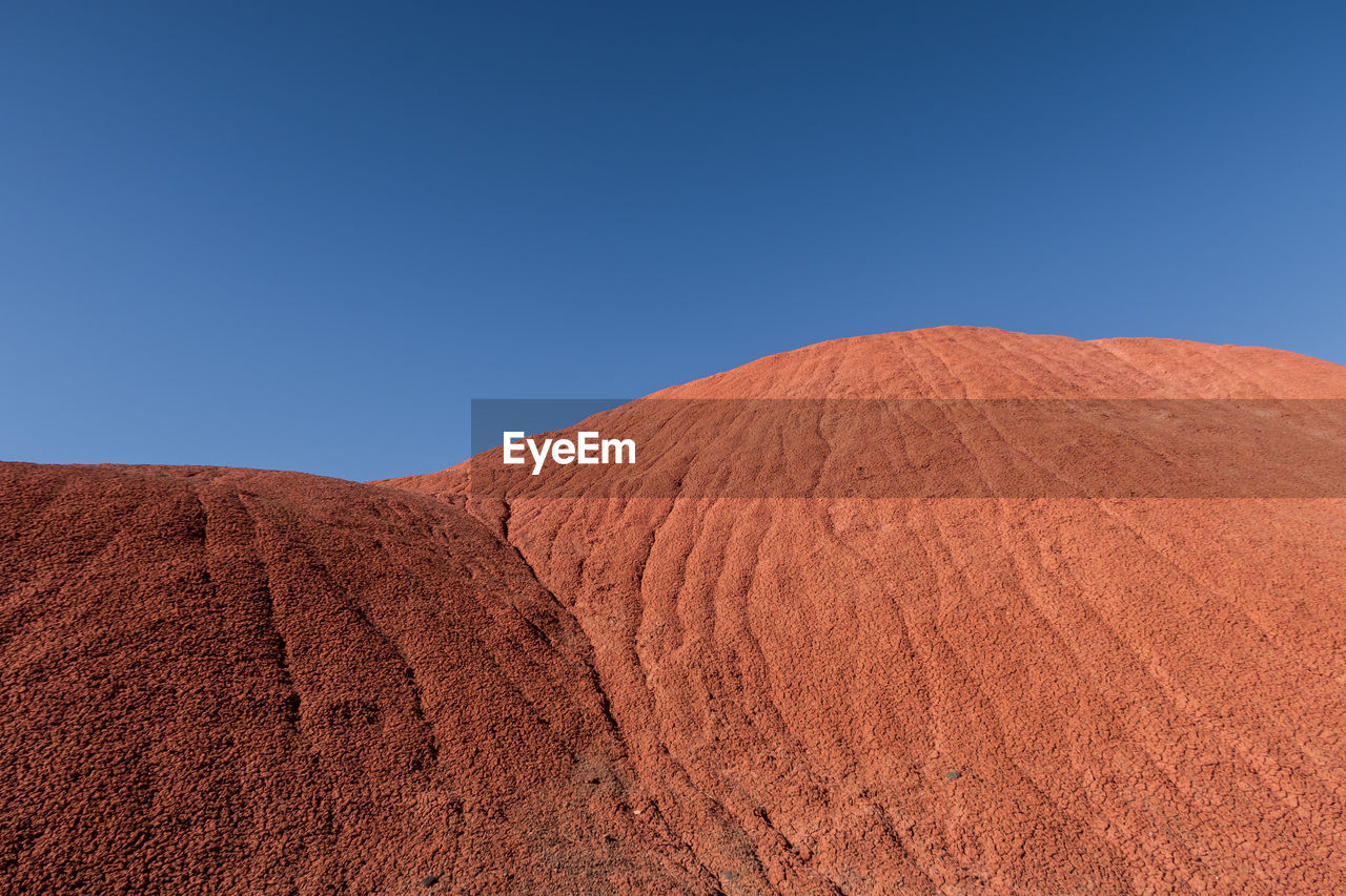 Scenic view of red hills in desert against clear blue sky