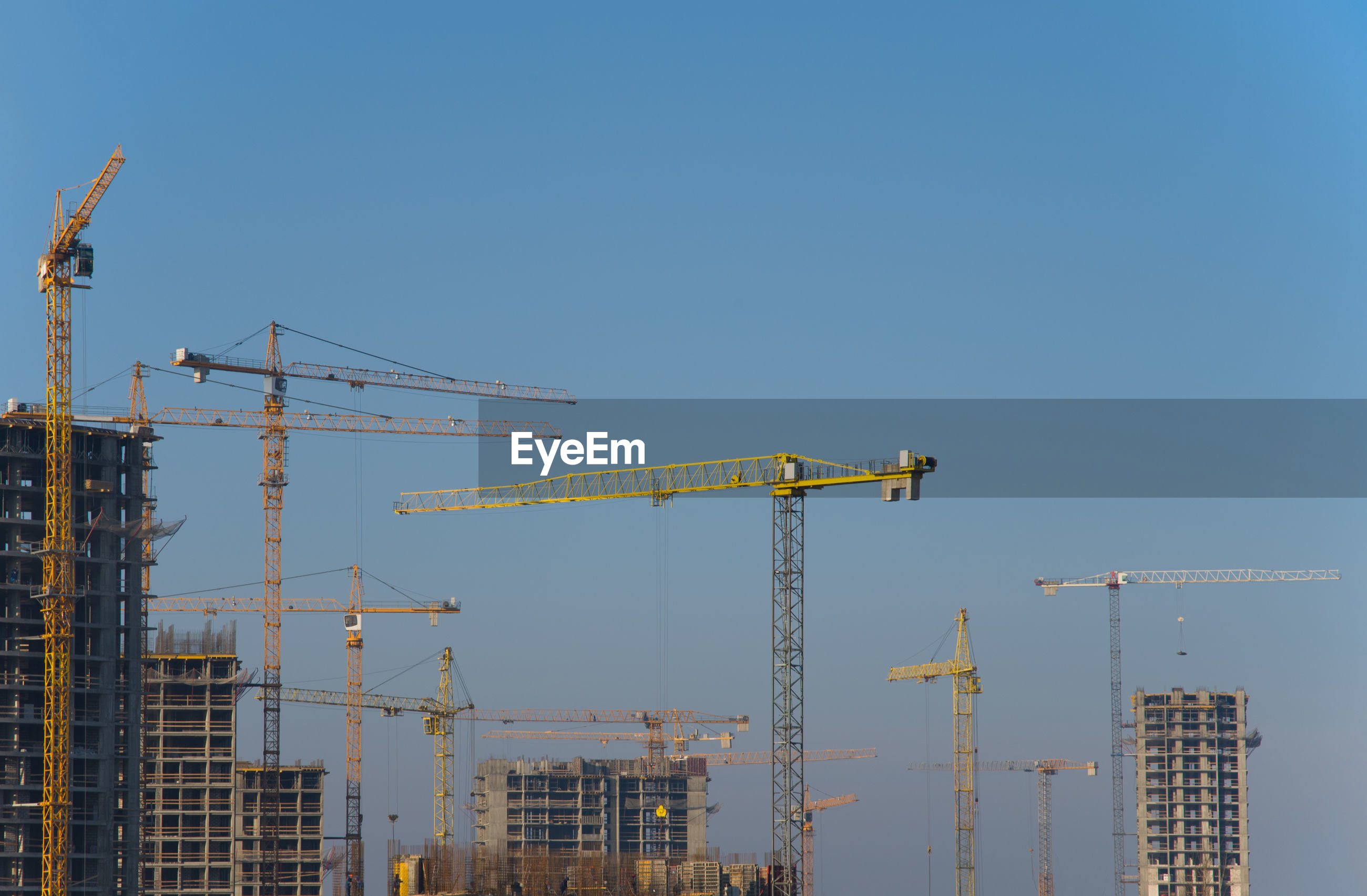 CRANES AND BUILDINGS AGAINST CLEAR BLUE SKY