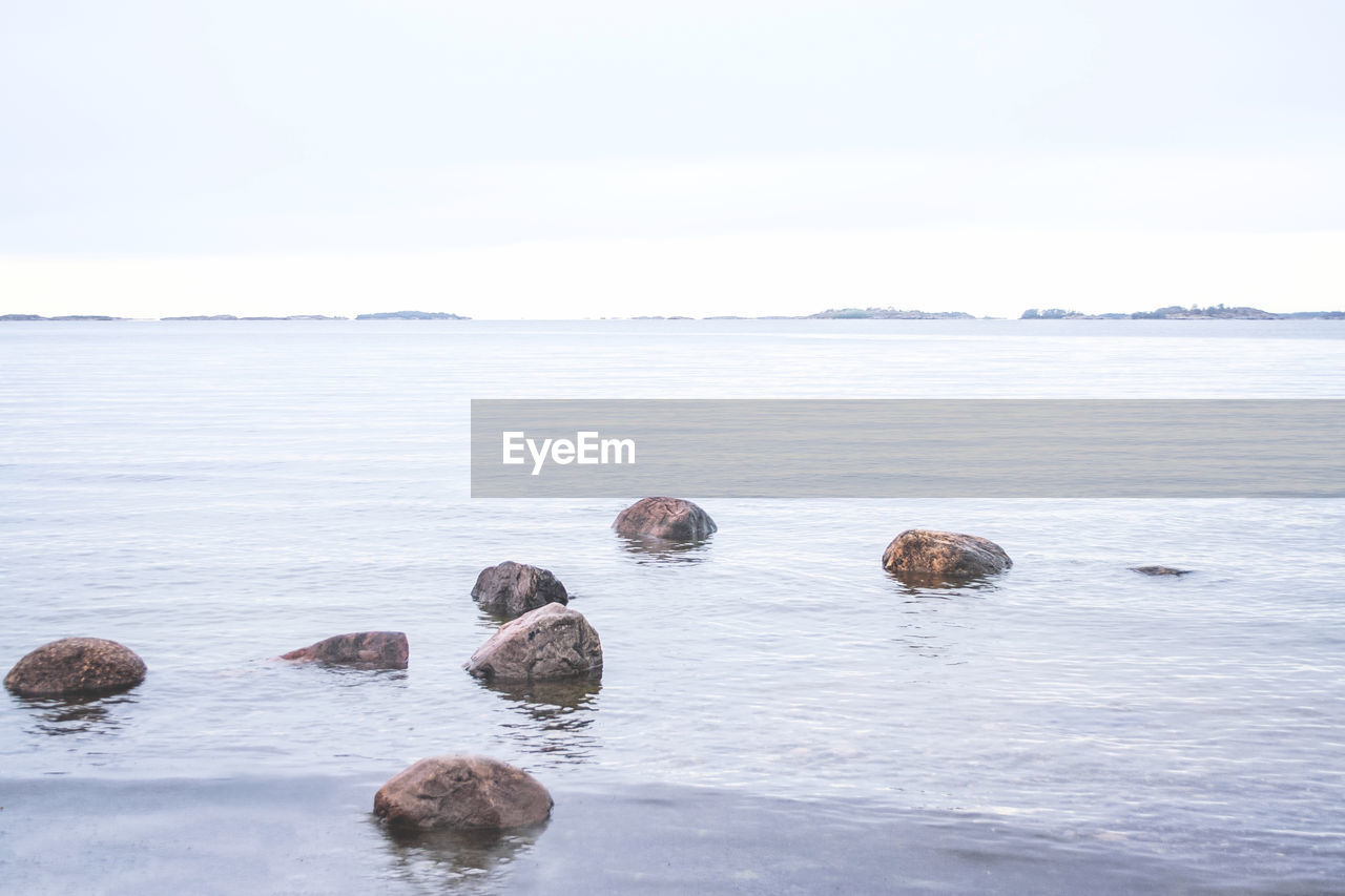 water, sky, sea, beauty in nature, day, nature, scenics - nature, rock, copy space, tranquil scene, no people, solid, tranquility, rock - object, waterfront, non-urban scene, outdoors, land, beach