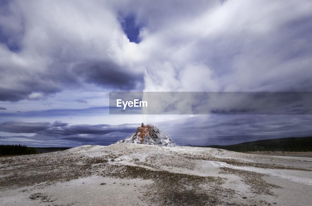 Steam Emitting From Geyser Against Cloudy Sky