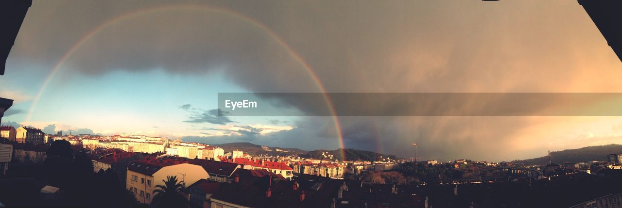 Panoramic View Of Rainbow Above Buildings At Sunset