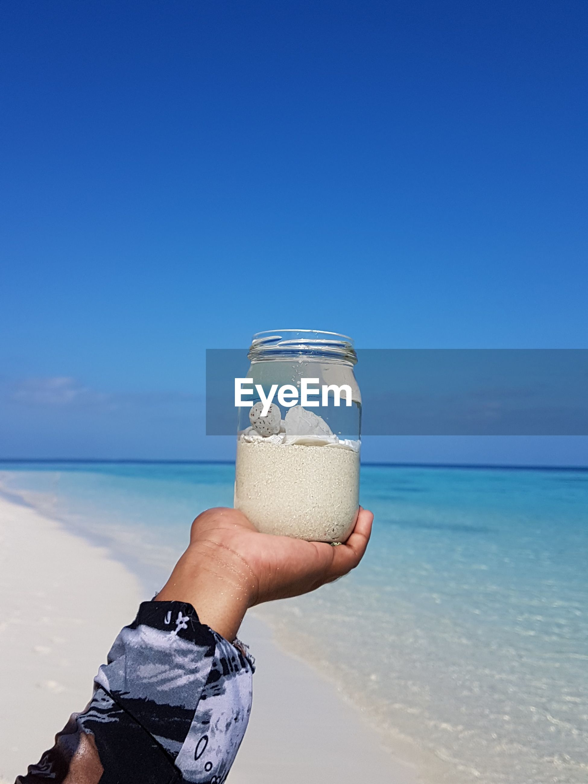 Girl holding glass of water at beach against blue sky