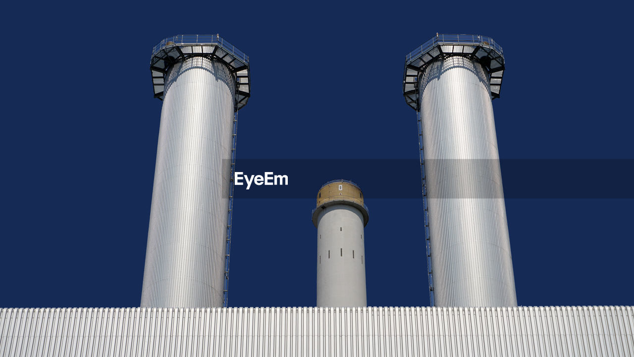 sky, clear sky, low angle view, no people, architecture, blue, built structure, industry, building exterior, factory, nature, environmental issues, day, smoke stack, tall - high, fuel and power generation, outdoors, environment, environmental damage, pollution, air pollution, silver colored