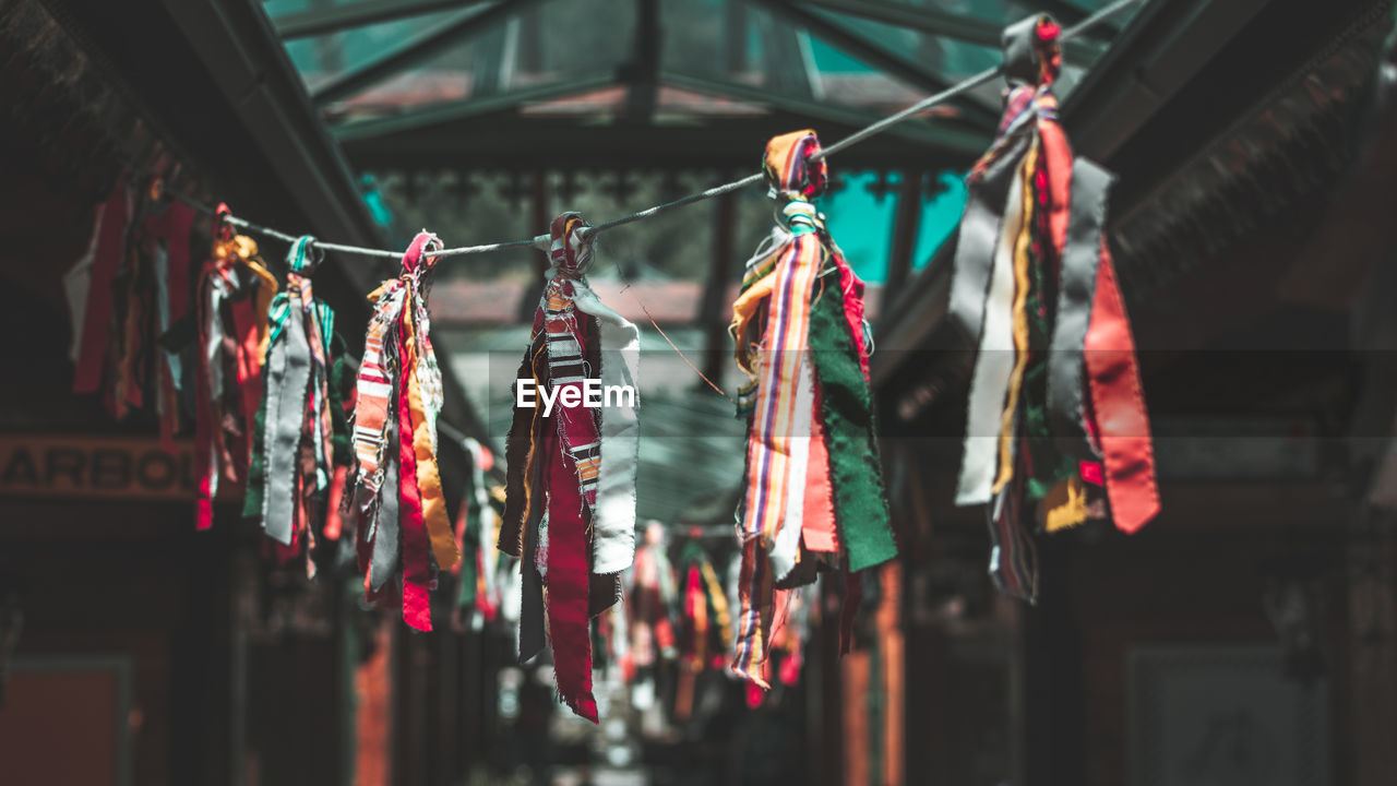 hanging, no people, focus on foreground, clothing, multi colored, architecture, rope, built structure, close-up, decoration, drying, day, clothesline, low angle view, string, building, side by side, large group of objects, building exterior, outdoors