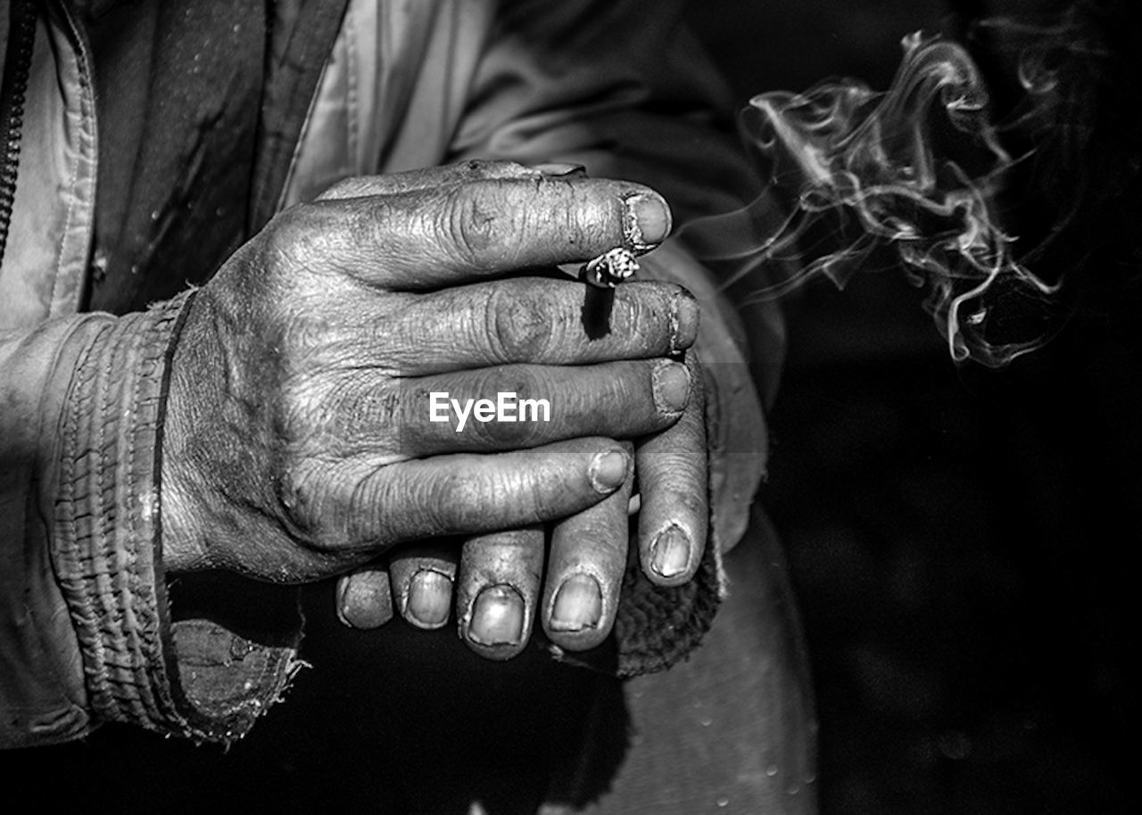 Cropped Hands Of Man Holding Cigarette