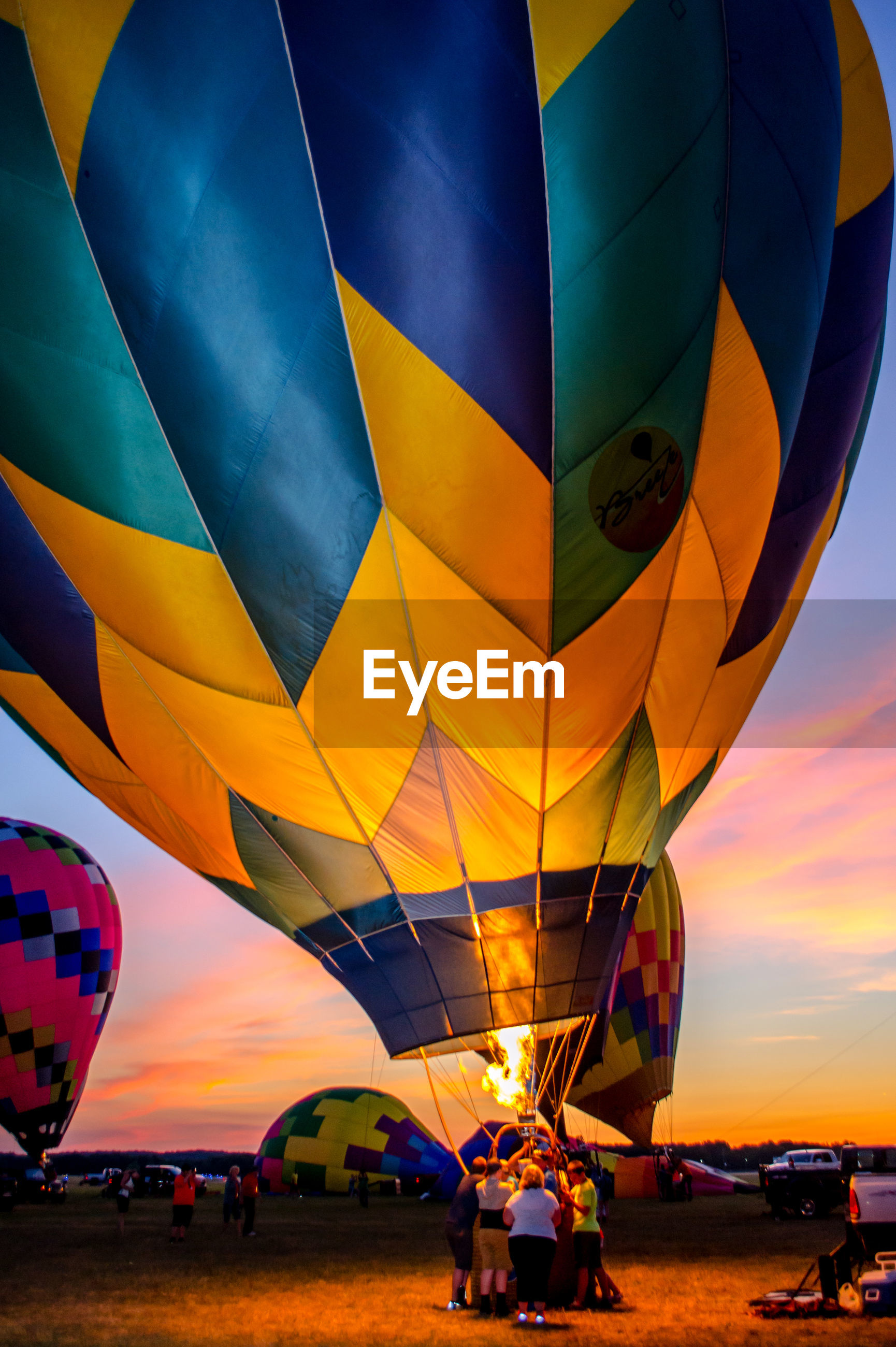 Multi colored hot air balloons against sky during sunset