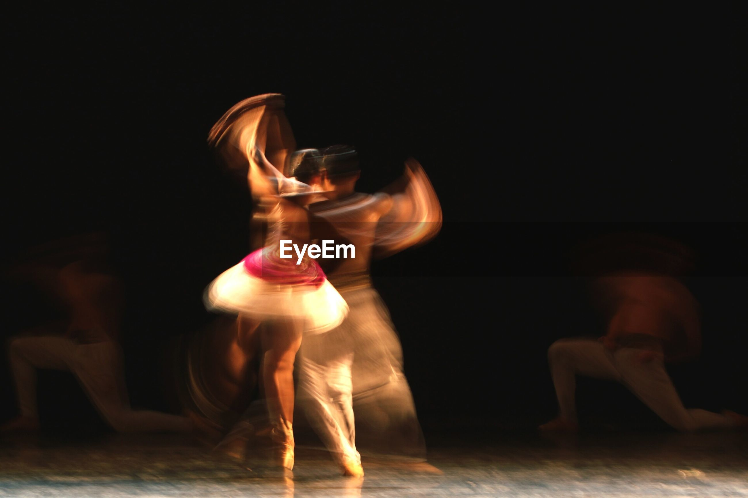Blurred motion of artists dancing on stage