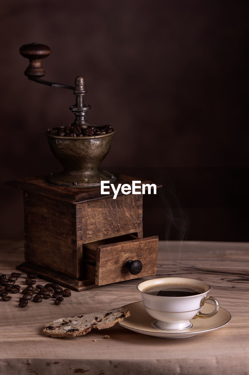 Coffee cup and maker on table