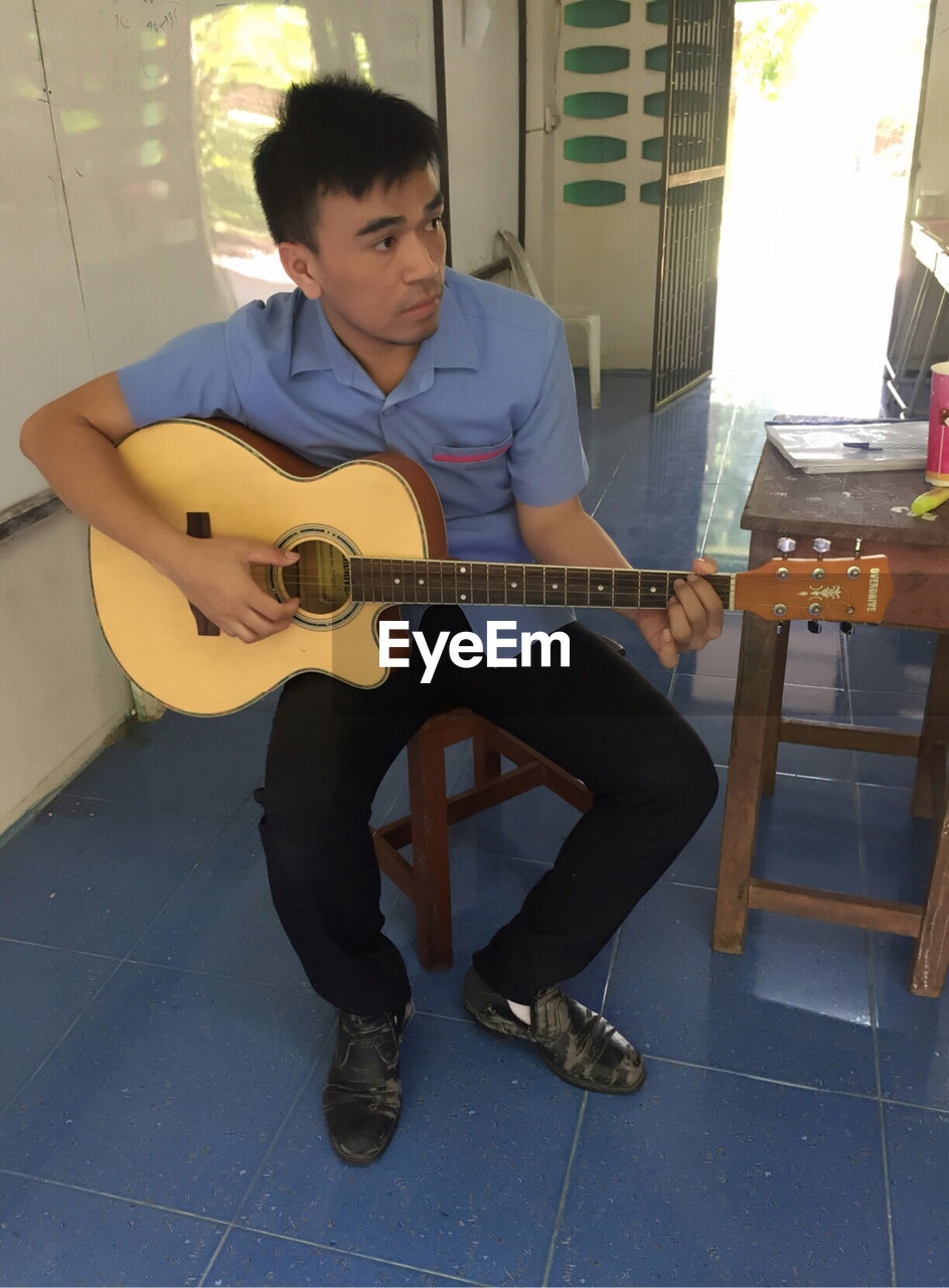 musical instrument, music, one person, sitting, guitar, playing, string instrument, real people, musical equipment, young men, young adult, full length, arts culture and entertainment, leisure activity, front view, casual clothing, lifestyles, indoors, musician, plucking an instrument, acoustic guitar