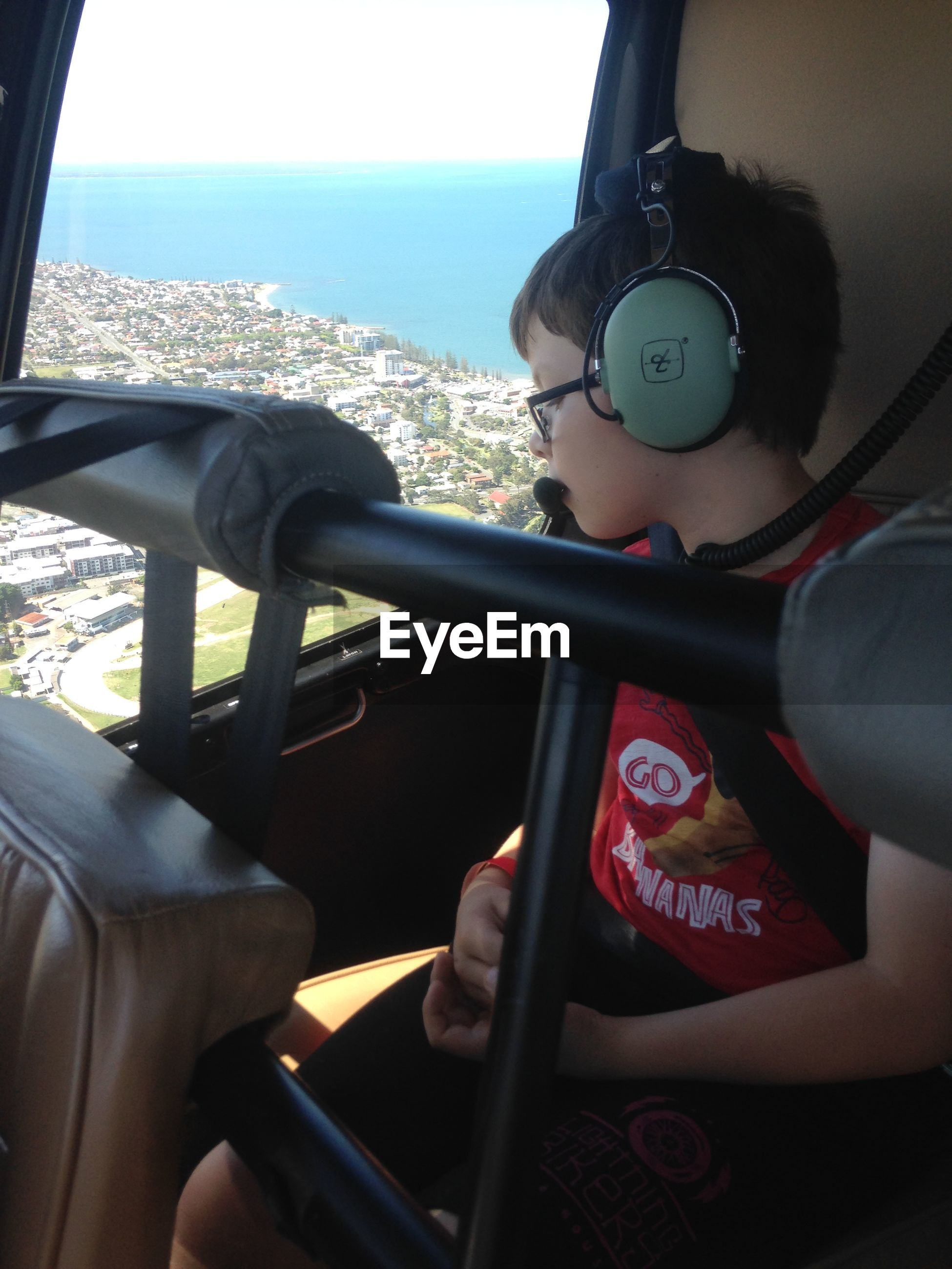 Boy with headphones sitting in airplane