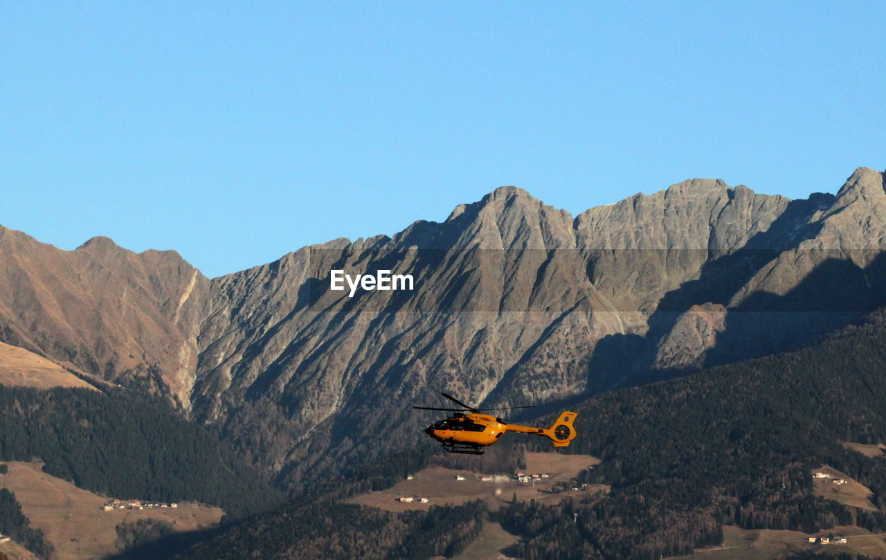 Helicopter flying over rocky mountains against clear sky