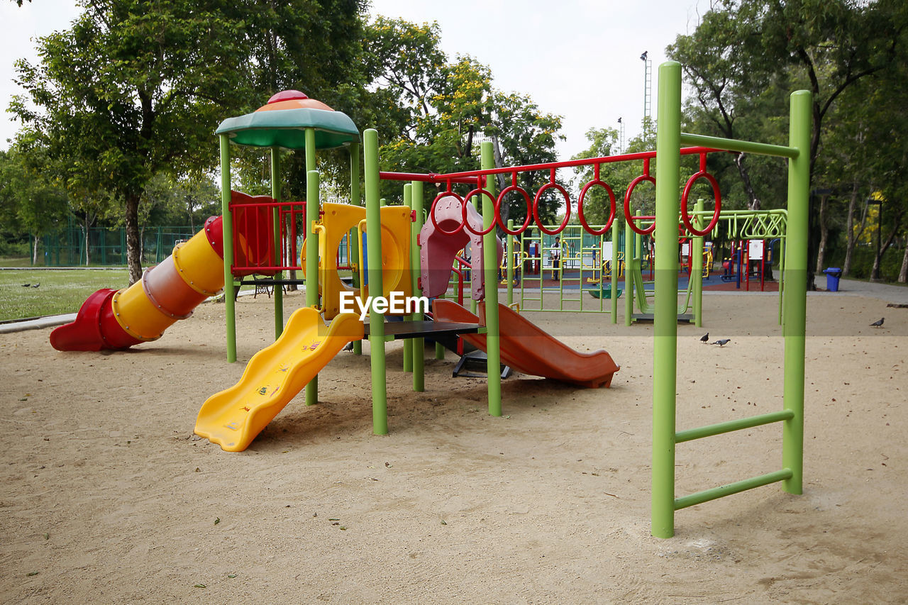 playground, childhood, tree, day, outdoor play equipment, sand, plant, slide, nature, slide - play equipment, park, jungle gym, park - man made space, empty, land, absence, red, yellow, sky, outdoors