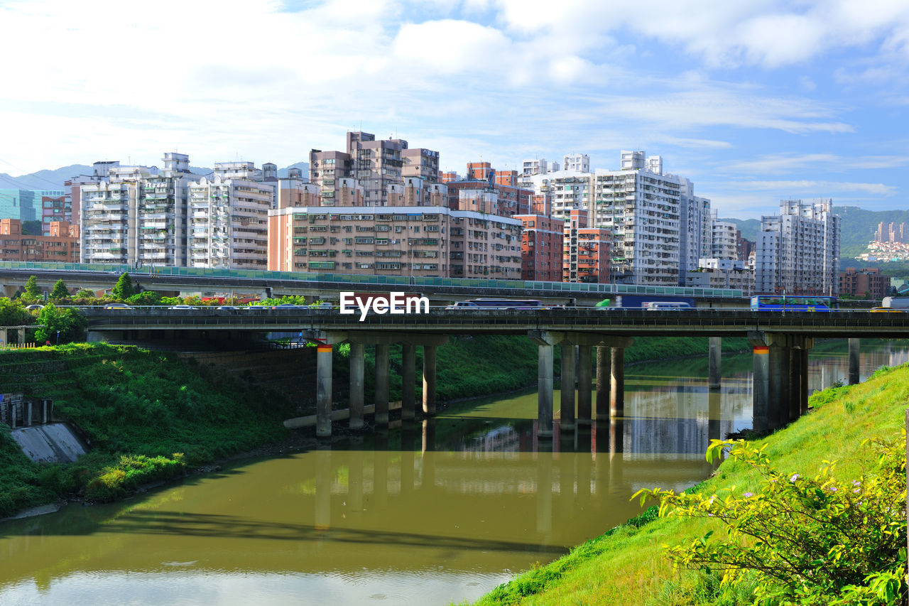 architecture, bridge - man made structure, connection, built structure, sky, water, day, outdoors, building exterior, river, no people, waterfront, cloud - sky, city, modern, tree, nature