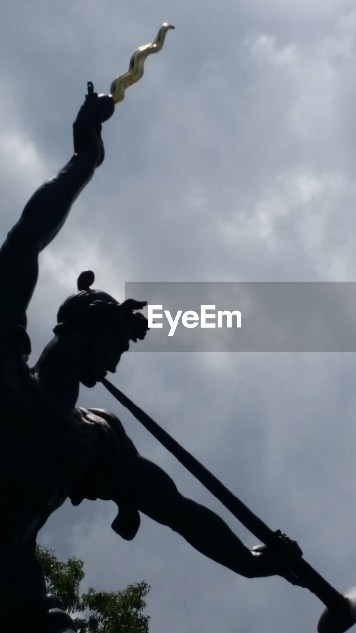 low angle view, cloud - sky, sky, silhouette, statue, outdoors, sculpture, day, tree, real people, nature, animal themes, mammal