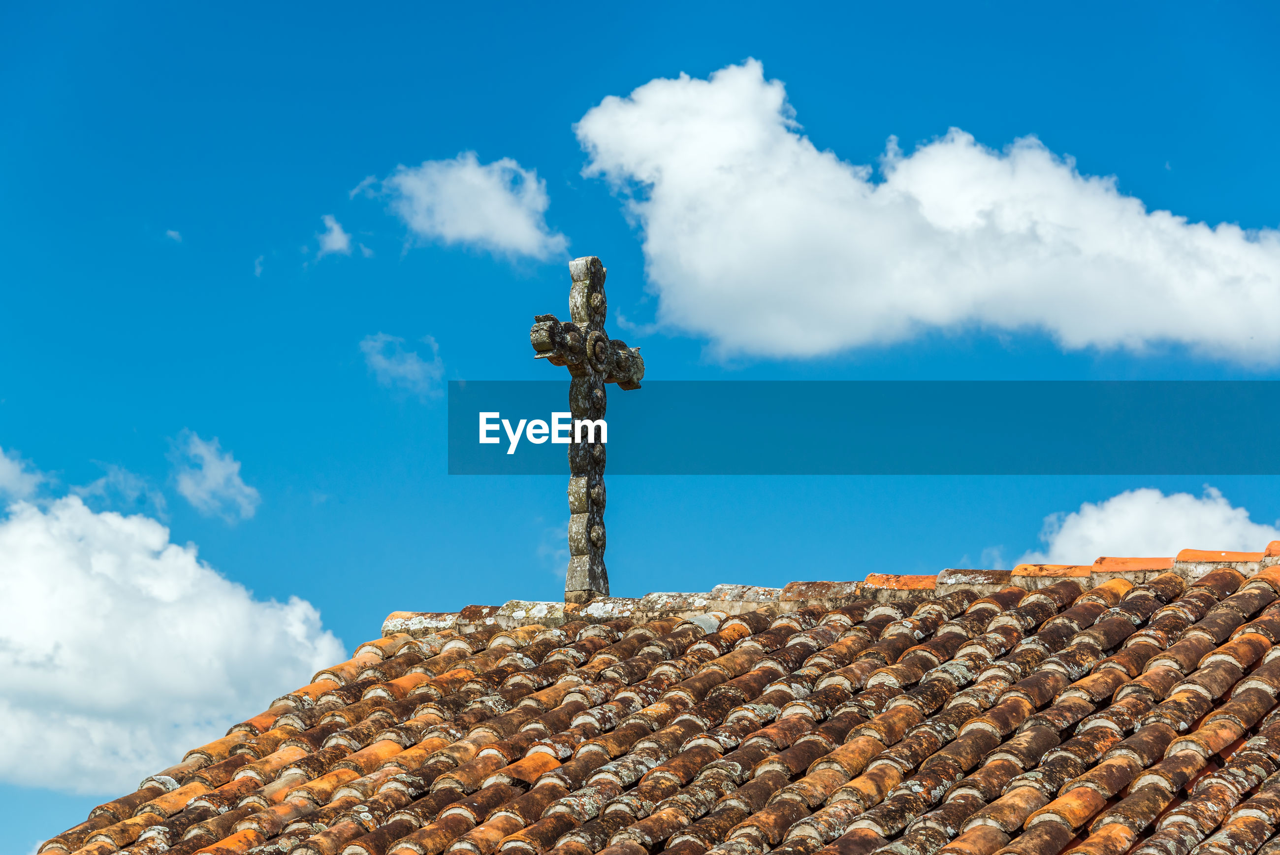 Low angle view of cross over roof tiles against sky