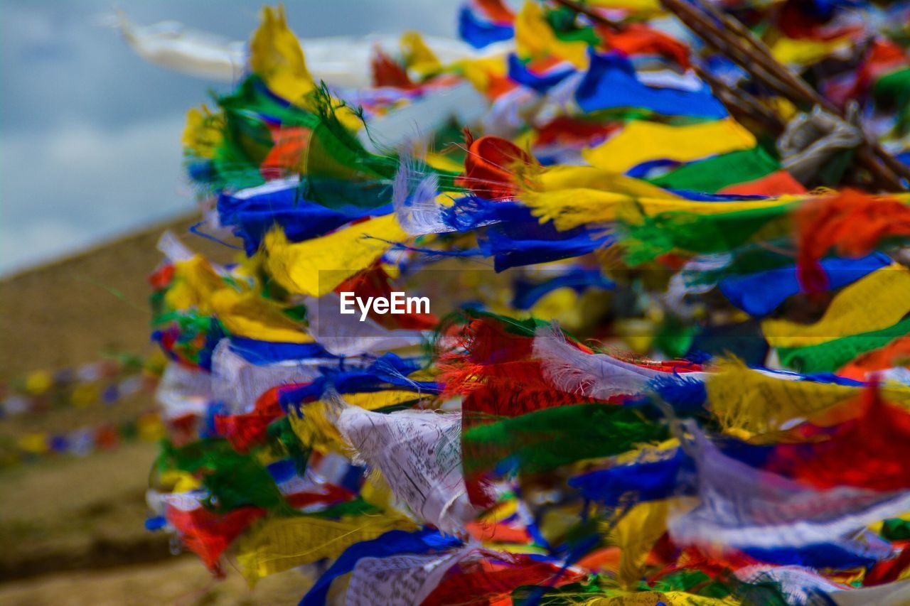 Close-up of multi colored prayer flags against blue sky