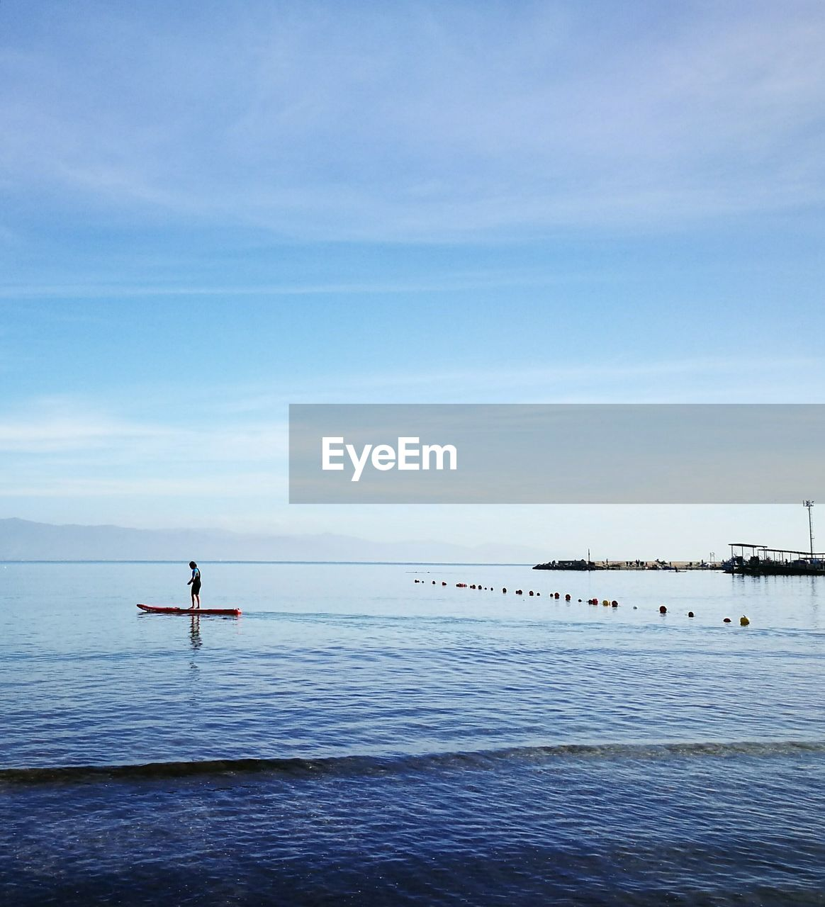 Woman Paddleboarding In Sea Against Sky