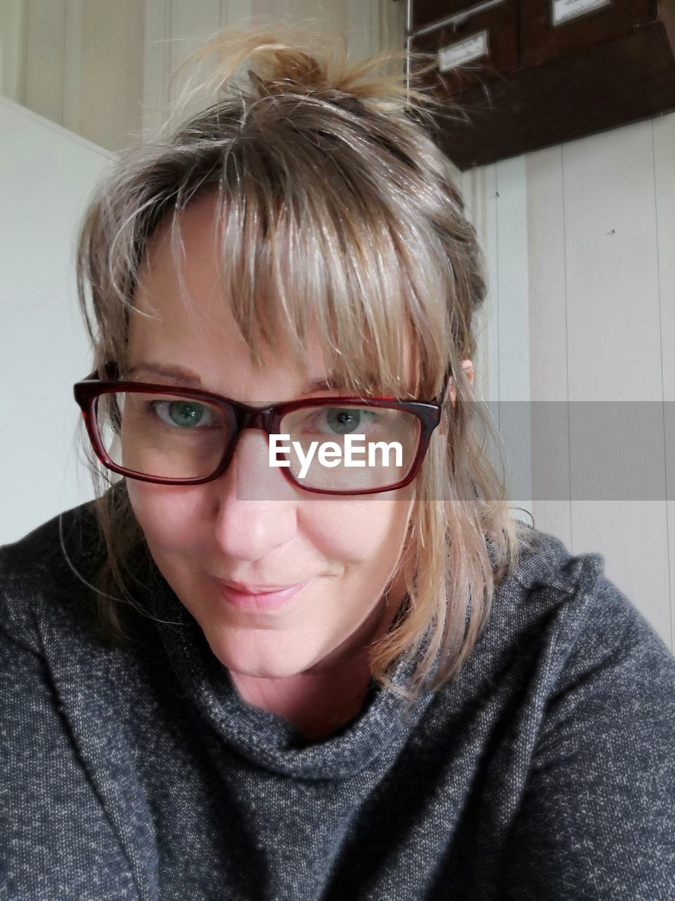 Close-up portrait of woman wearing eyeglasses at home