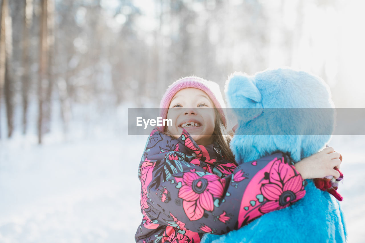 Close-Up Of Smiling Girl With Father On Snow