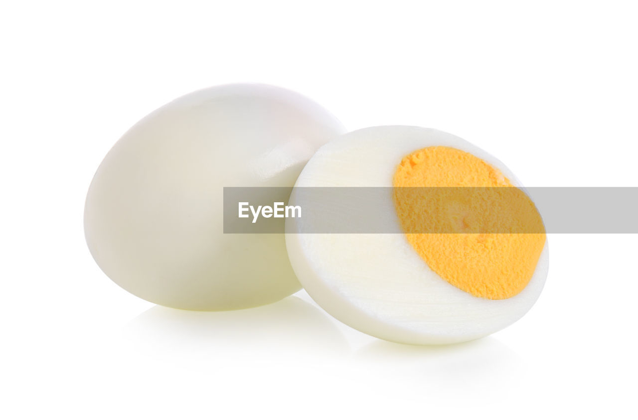 white background, studio shot, still life, indoors, food, close-up, healthy eating, cut out, food and drink, freshness, wellbeing, egg, no people, ingredient, yellow, raw food, copy space, two objects, boiled egg, boiled, egg yolk