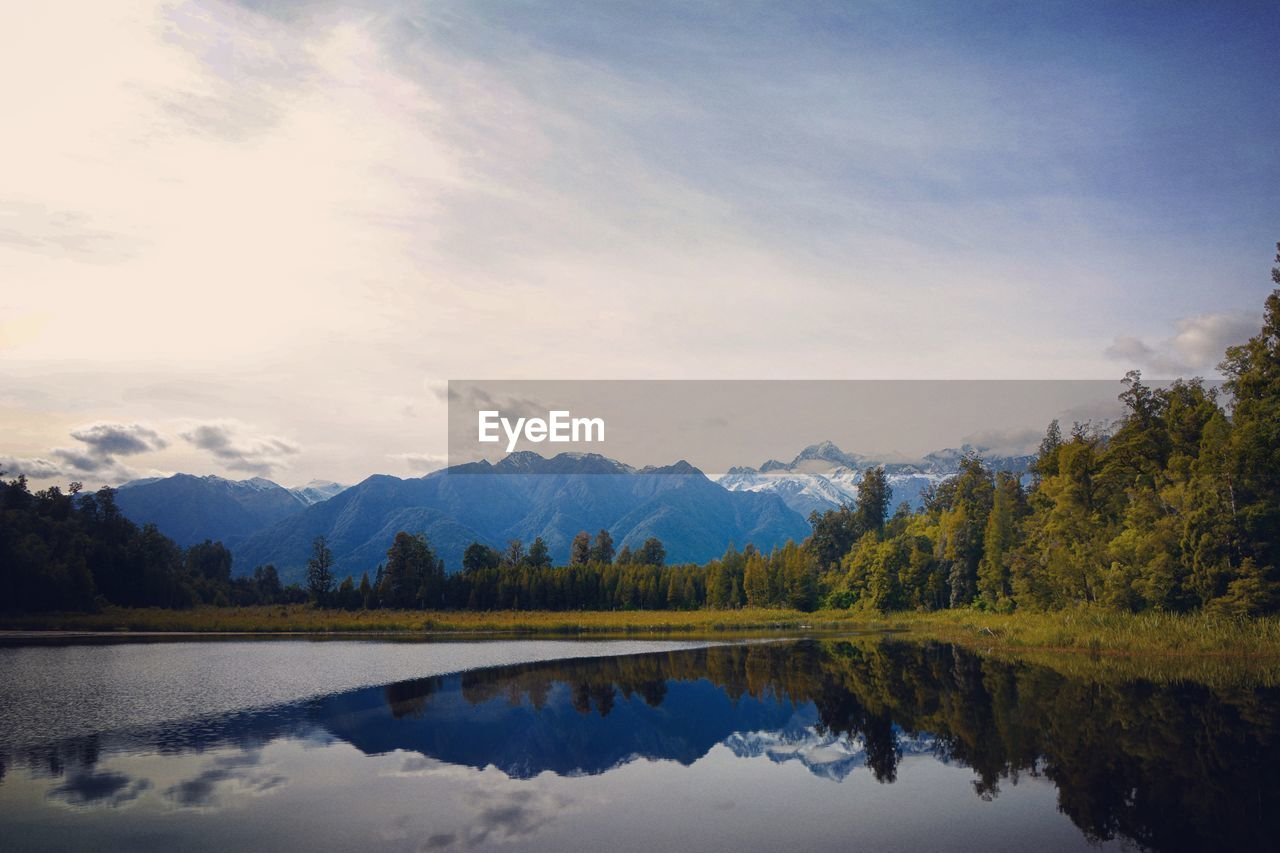 sky, tranquility, lake, beauty in nature, tranquil scene, cloud - sky, scenics - nature, reflection, water, tree, mountain, plant, non-urban scene, nature, waterfront, idyllic, no people, mountain range, day, outdoors, reflection lake