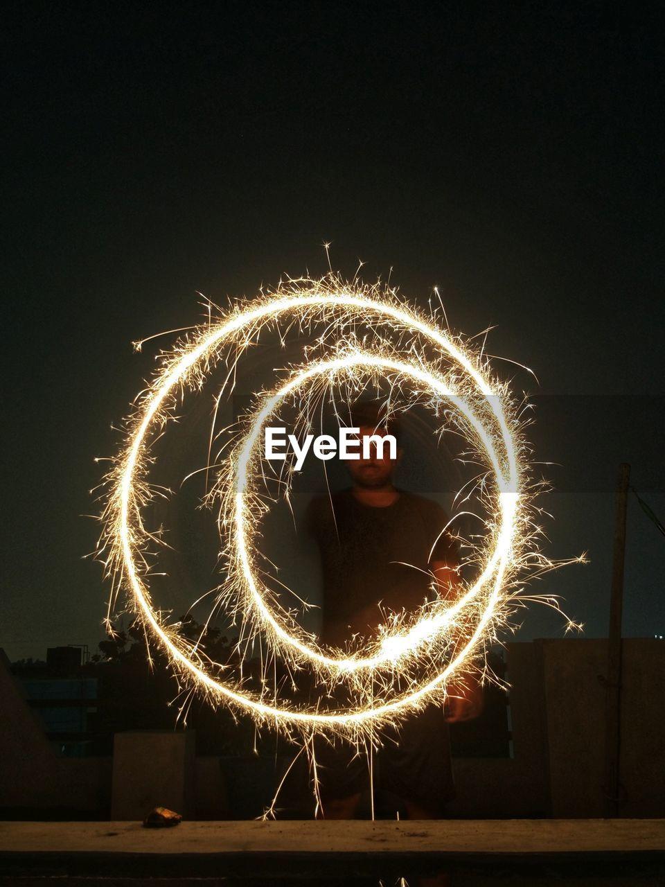 Man Spinning Sparkler At Night