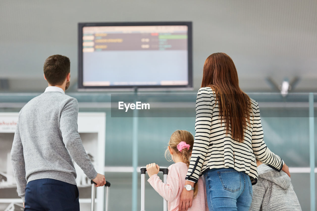 Rear view of family looking at arrival departure board in airport