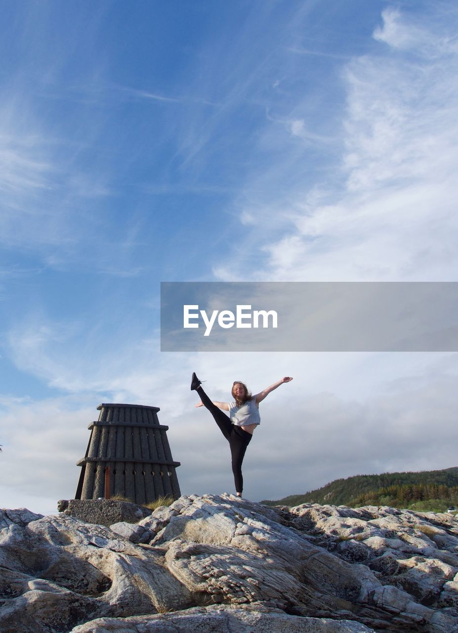 Full length of teenage girl practicing yoga on rocks against sky