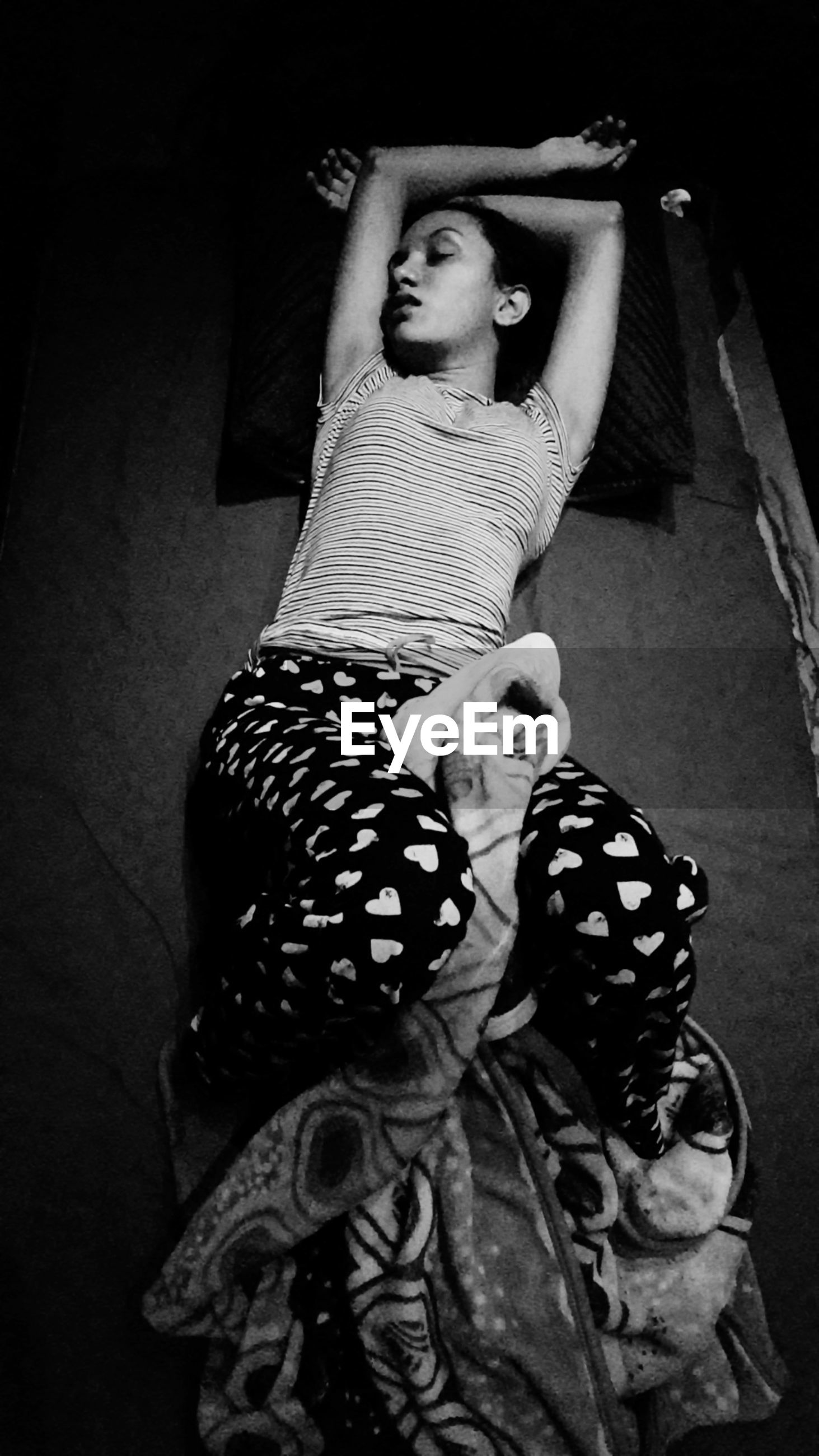 High angle view of girl sleeping on bed in darkroom