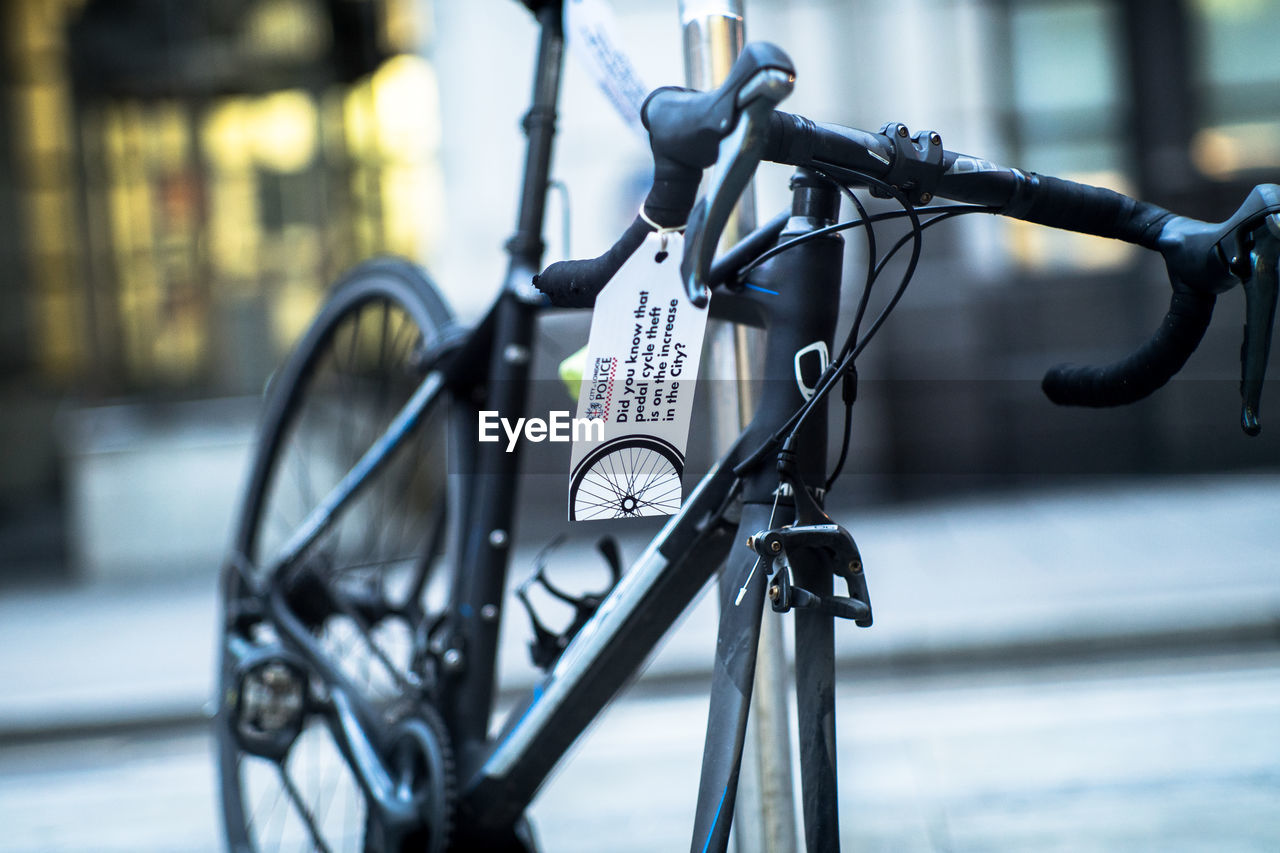 bicycle, mode of transport, transportation, land vehicle, stationary, focus on foreground, metal, text, day, city, no people, outdoors, bicycle rack, built structure, architecture, close-up
