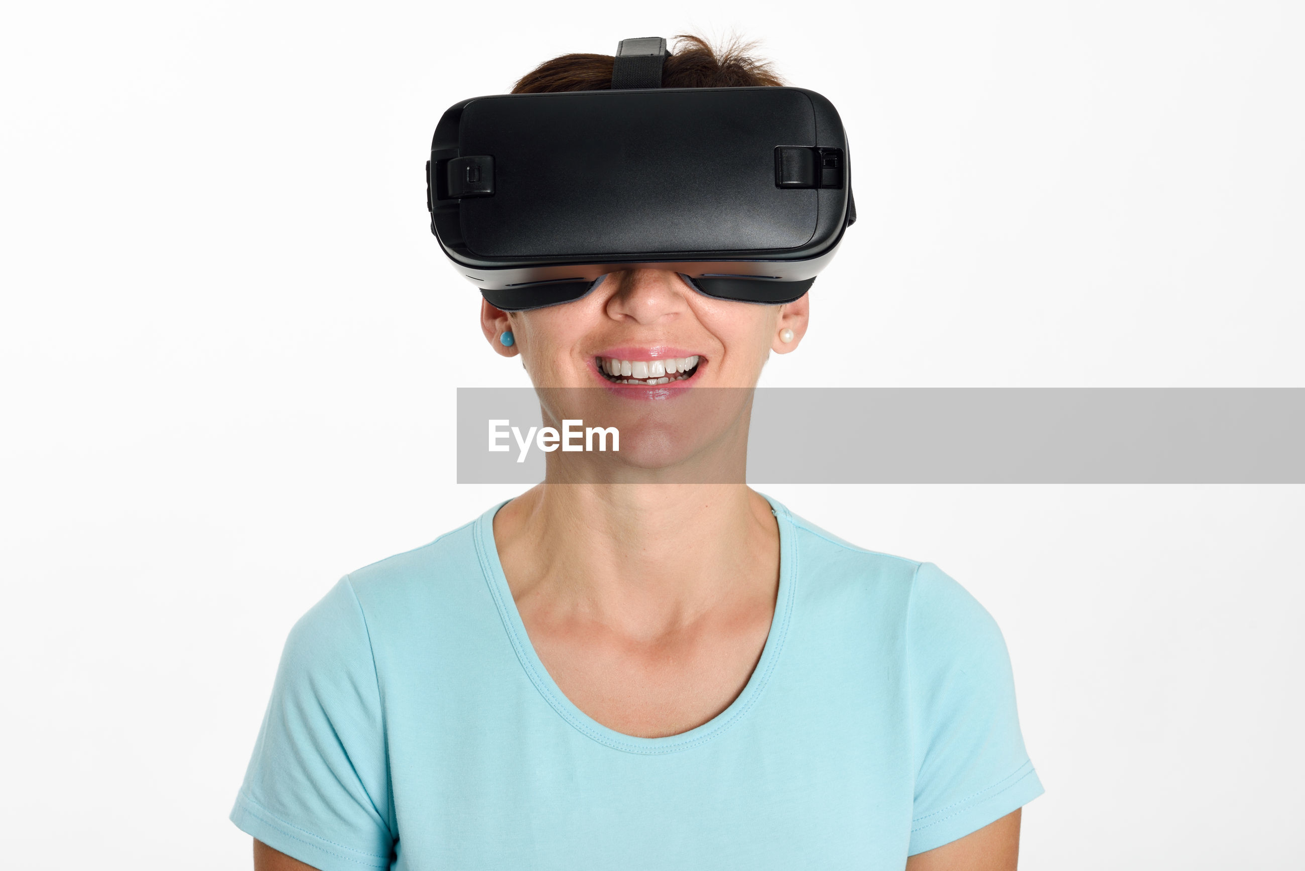 Smiling mature woman using virtual reality against white background
