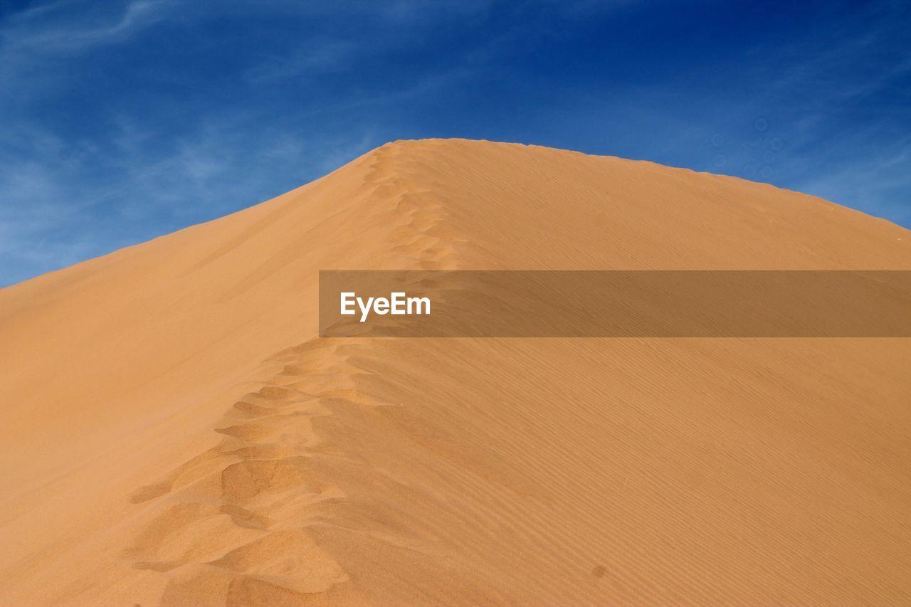 Sand Dune In Sahara Desert Against Blue Sky