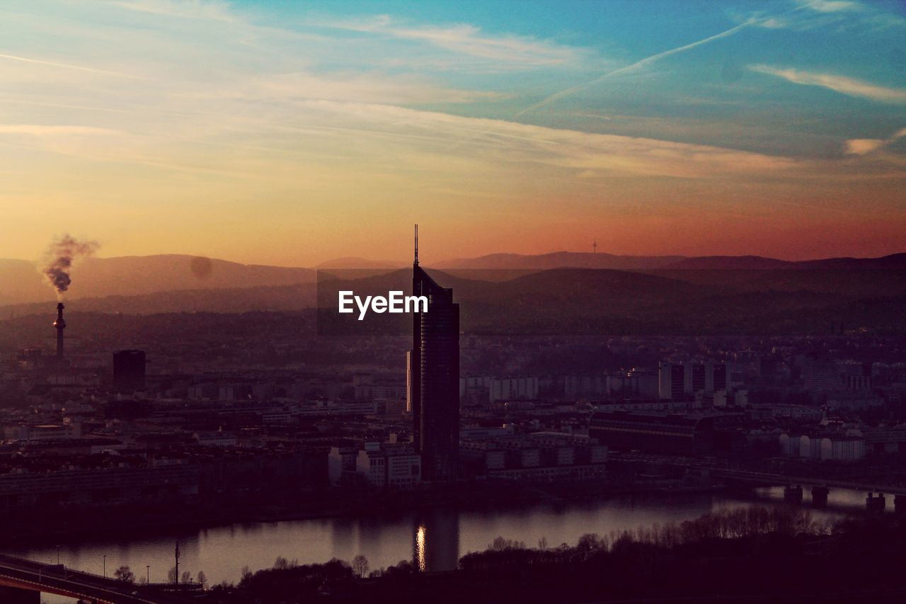 architecture, sky, sunset, built structure, city, building exterior, no people, river, connection, water, cityscape, travel destinations, cloud - sky, outdoors, nature, mountain, day
