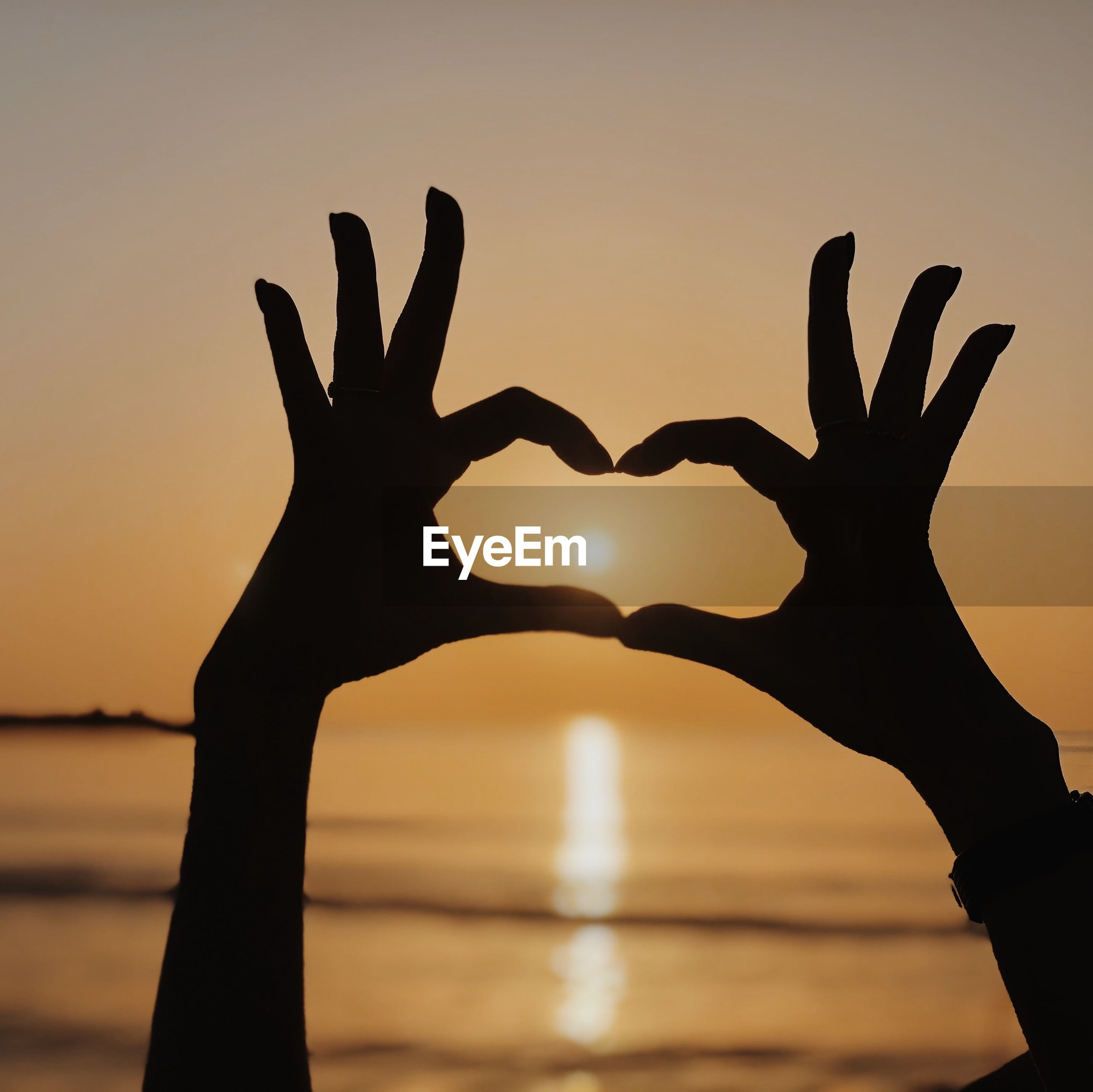 Cropped hands gesturing heart shape against sky during sunset
