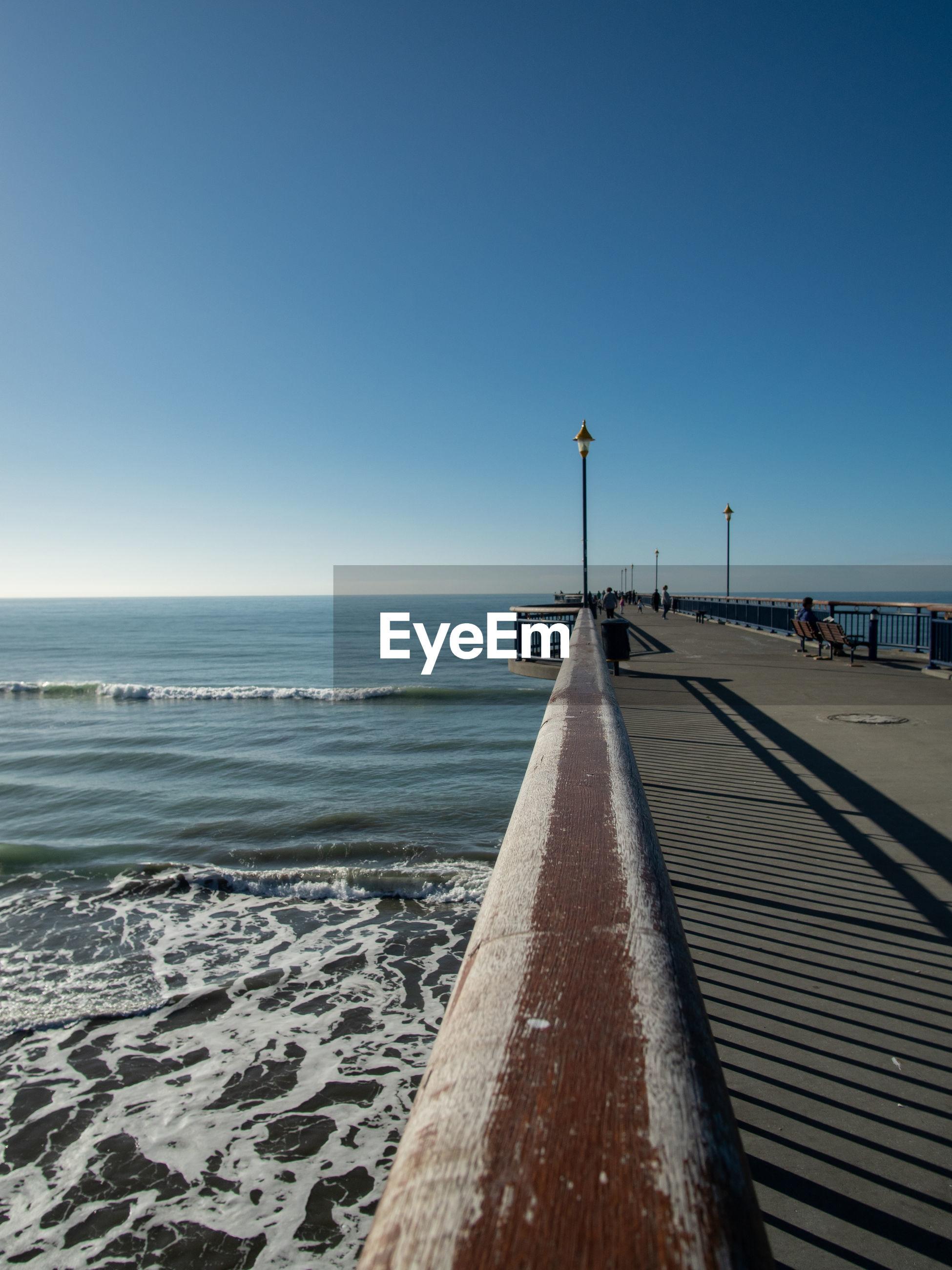 PIER ON BEACH AGAINST CLEAR BLUE SKY