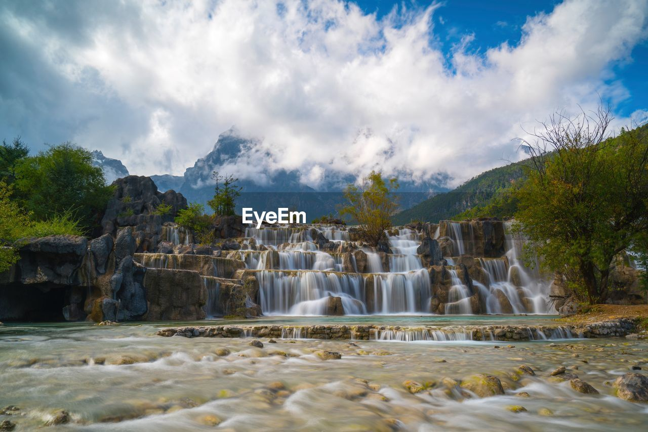 water, sky, scenics - nature, cloud - sky, beauty in nature, nature, waterfall, mountain, flowing water, day, motion, tree, flowing, long exposure, rock, no people, environment, blurred motion, non-urban scene, outdoors, power in nature, falling water
