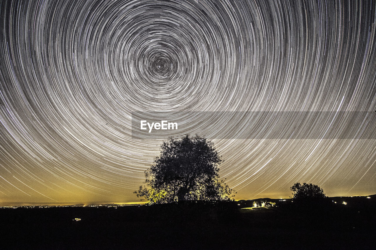 long exposure, star trail, night, motion, tree, scenics, blurred motion, nature, tranquil scene, beauty in nature, outdoors, no people, astronomy, silhouette, tranquility, illuminated, sky, star - space, concentric