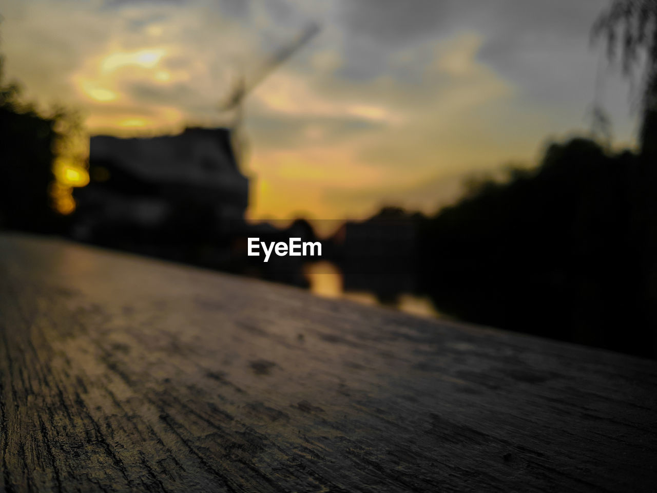 sunset, sky, wood - material, cloud - sky, orange color, nature, focus on foreground, close-up, outdoors, no people, selective focus, built structure, water, surface level, architecture, city, beauty in nature, textured, tranquility, sunlight