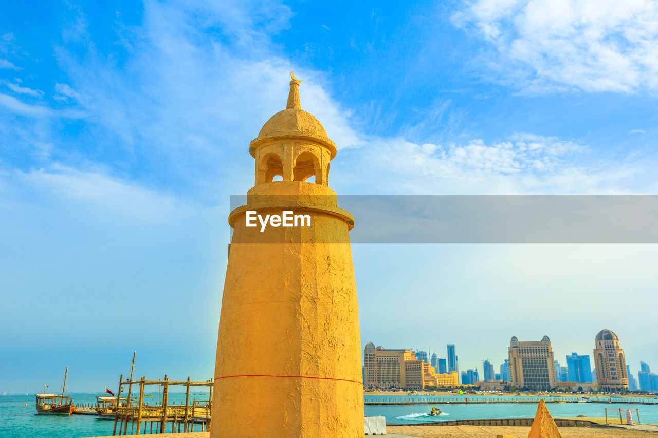 sky, built structure, architecture, building exterior, cloud - sky, day, nature, low angle view, building, no people, city, blue, tower, yellow, outdoors, travel destinations, travel, sunlight, industry, factory, skyscraper