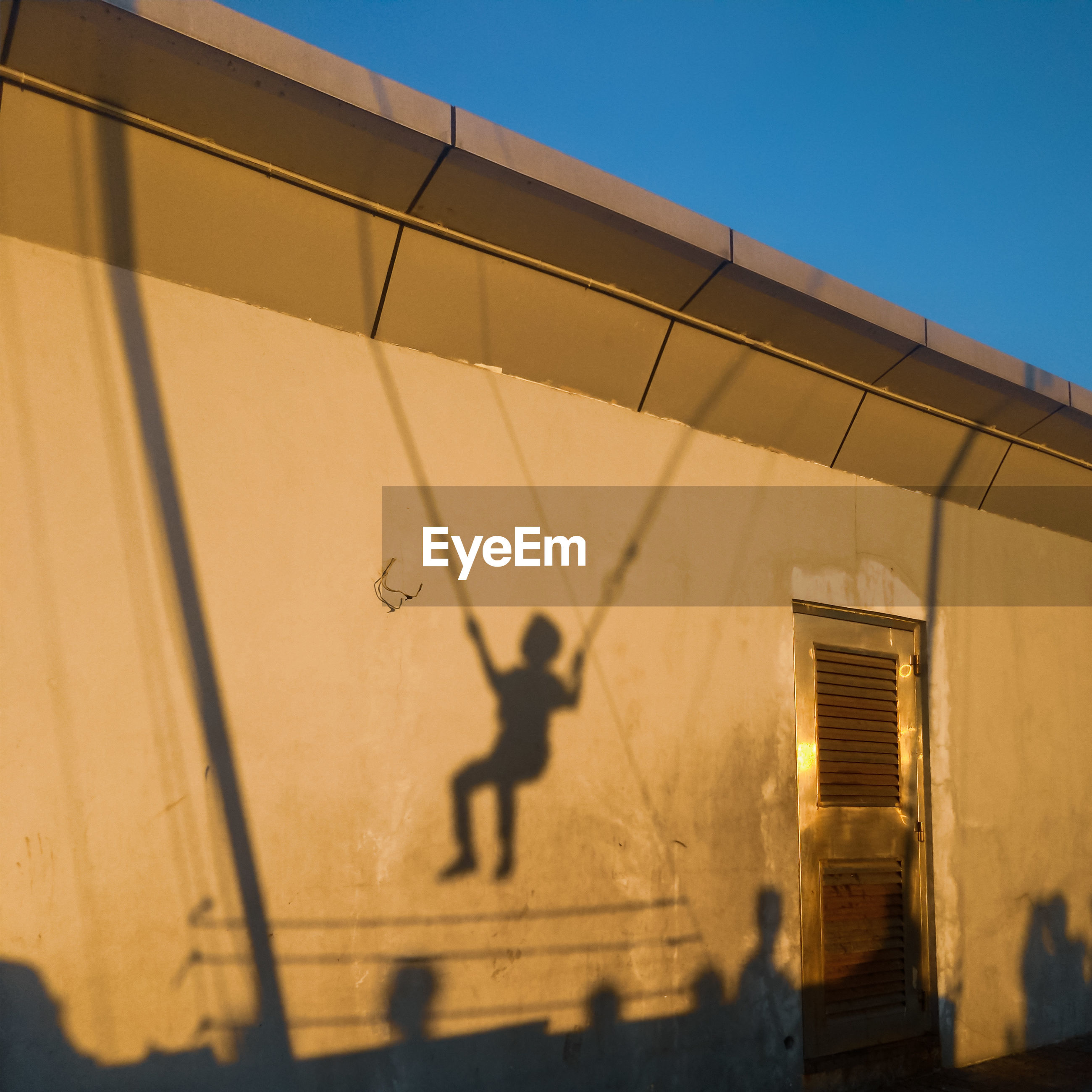 Low angle view of building with child shadow against sky on sunny day