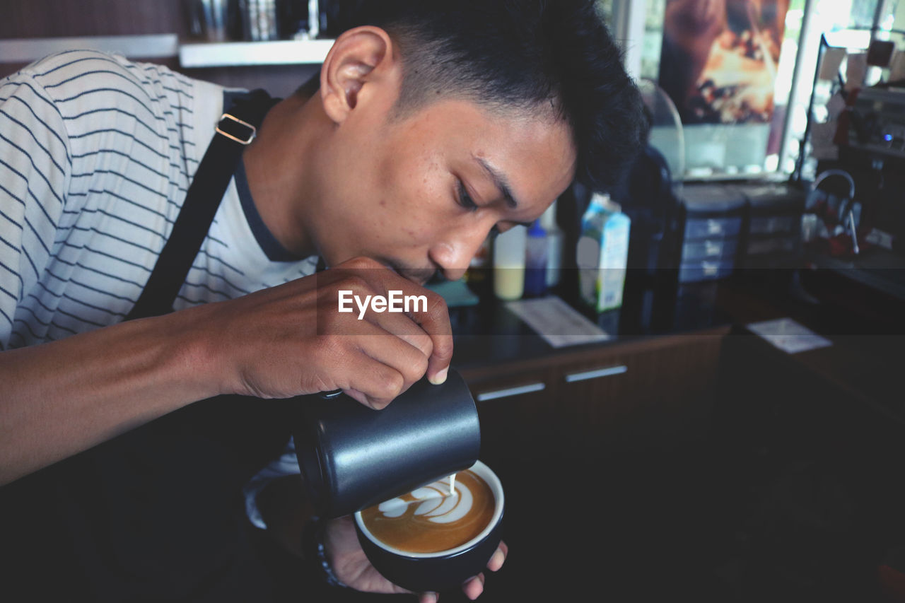 Man Pouring Milk In Coffee At Cafe