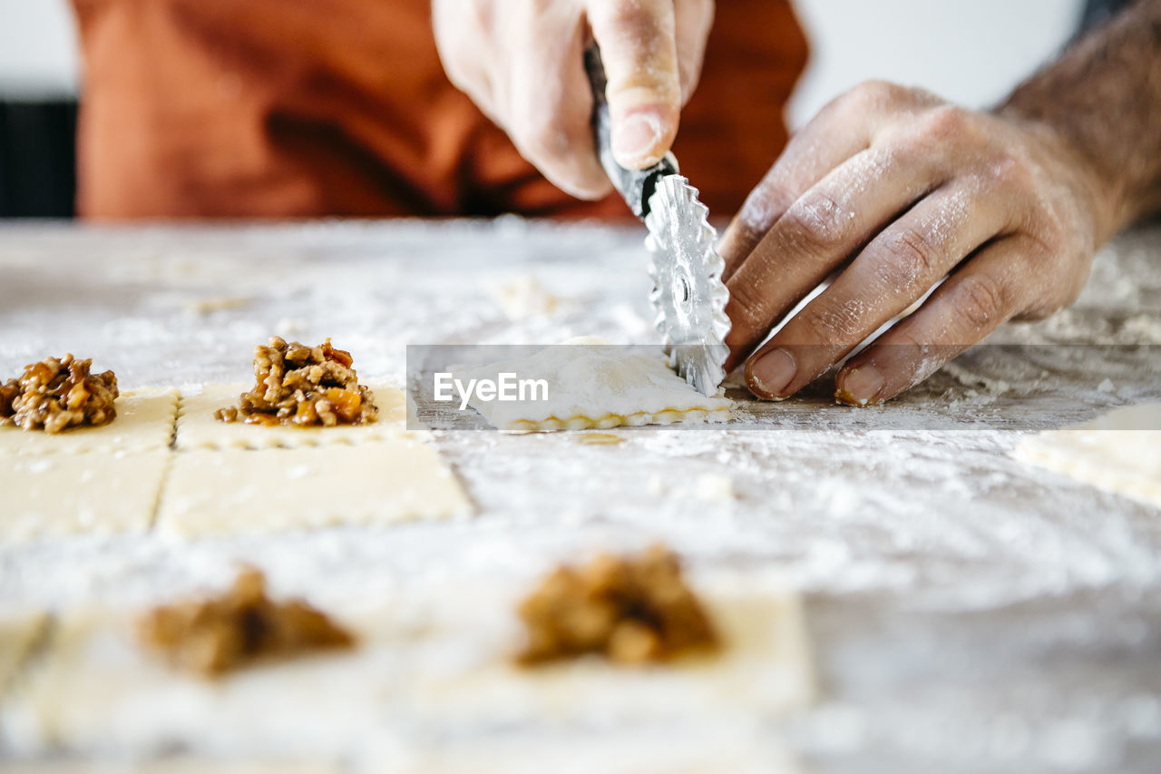 Cropped Hands Of Male Chef Preparing Food On Table