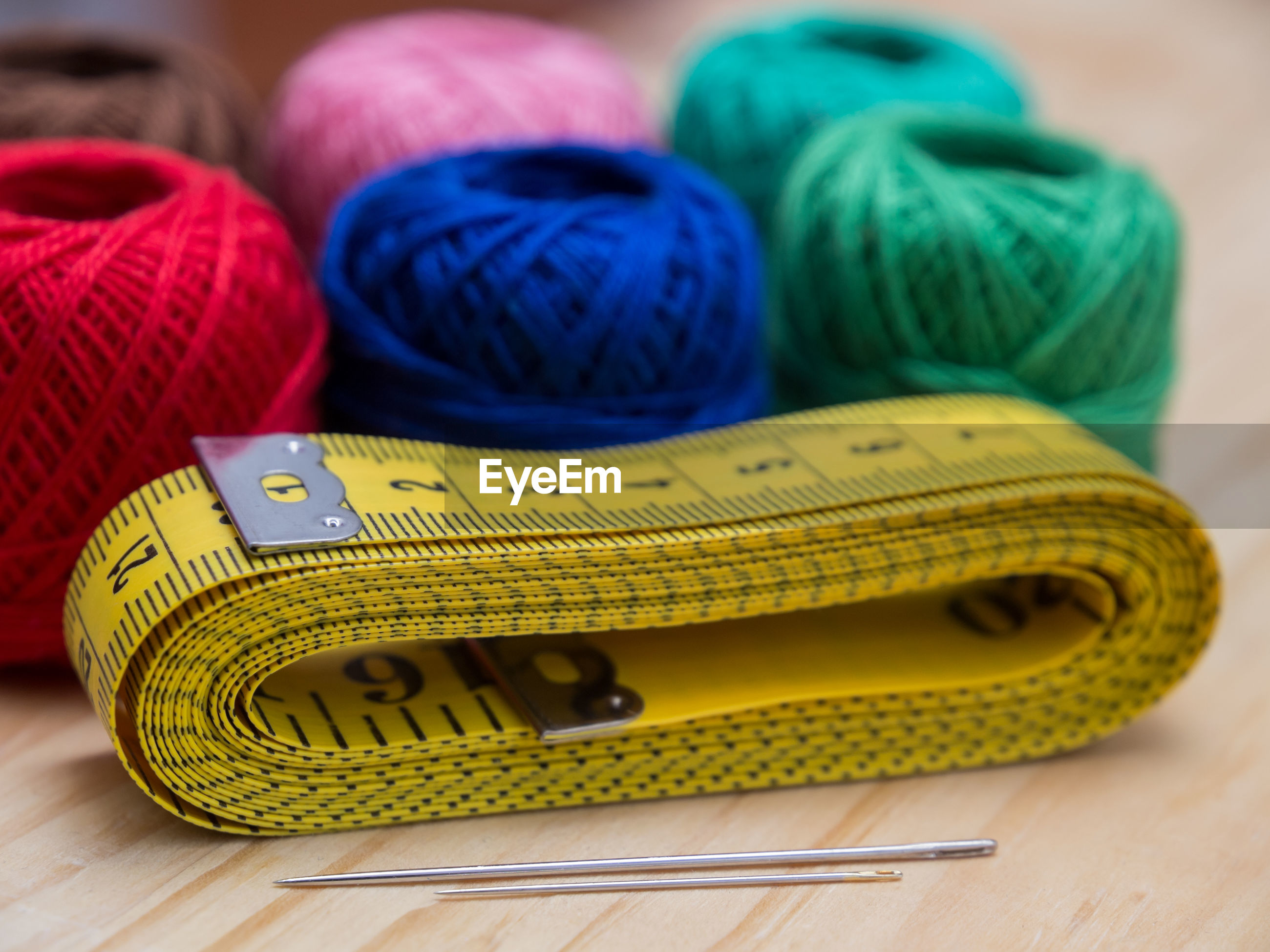 Close-up of tape measure with needles and multi colored wool ball on table