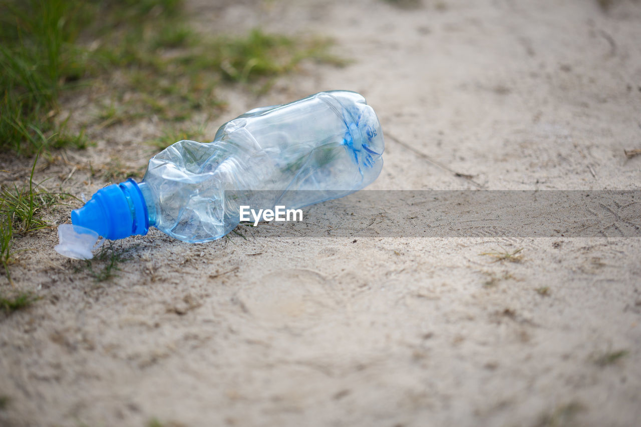 CLOSE-UP OF WATER BOTTLE ON GLASS OF SAND