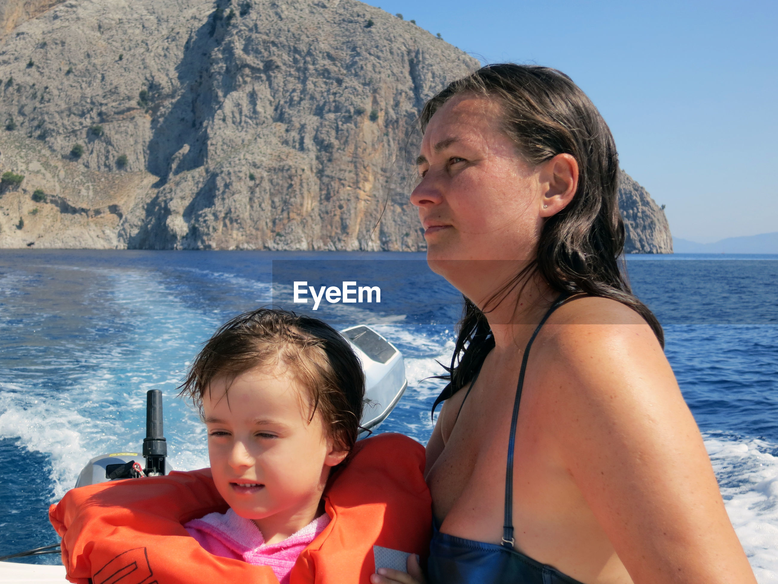 Woman with daughter on motorboat sailing in sea