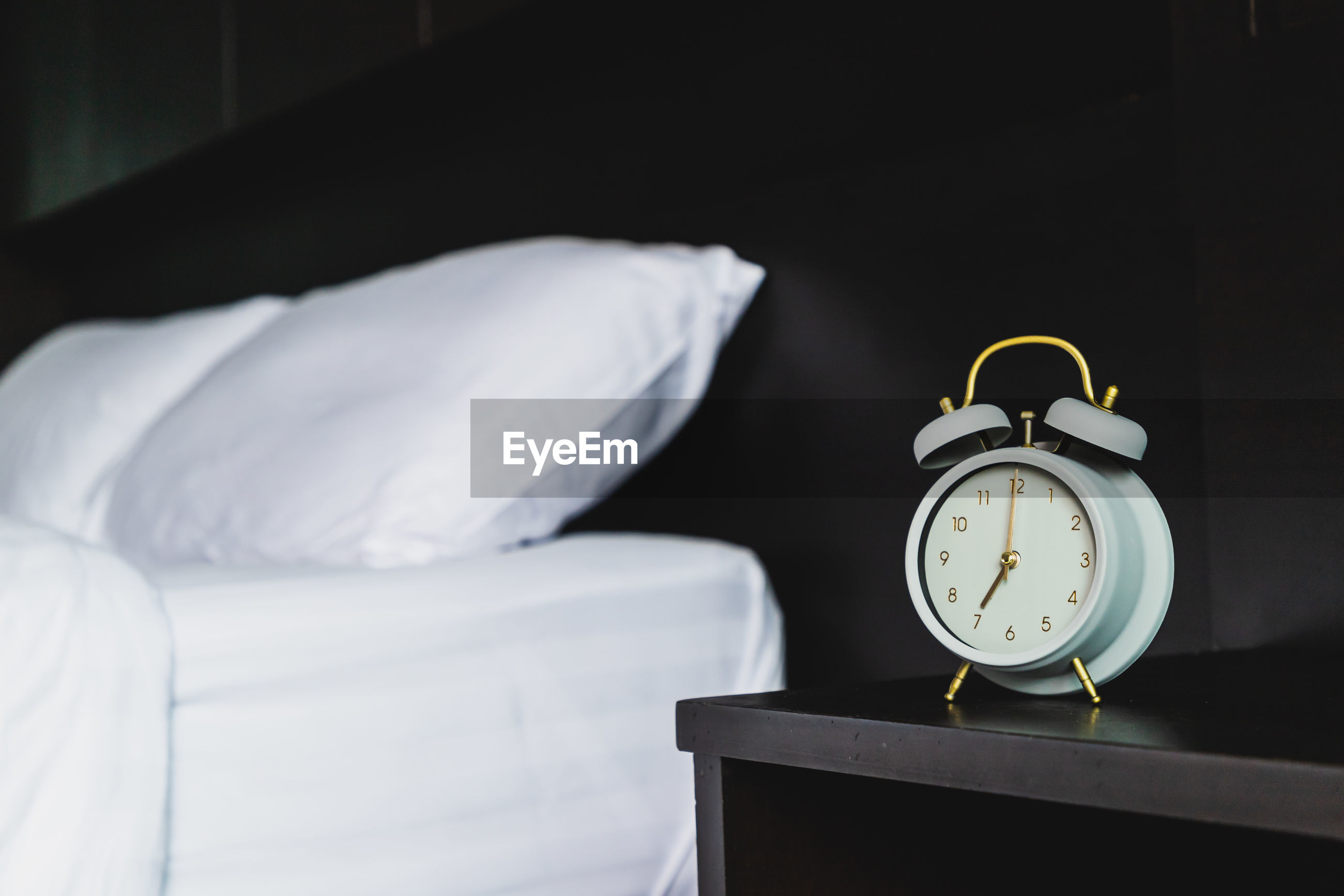 Close-up of alarm clock on night table against bed