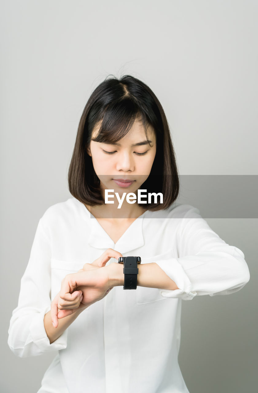 Young Woman Checking Time On Wristwatch While Standing Against Gray Background