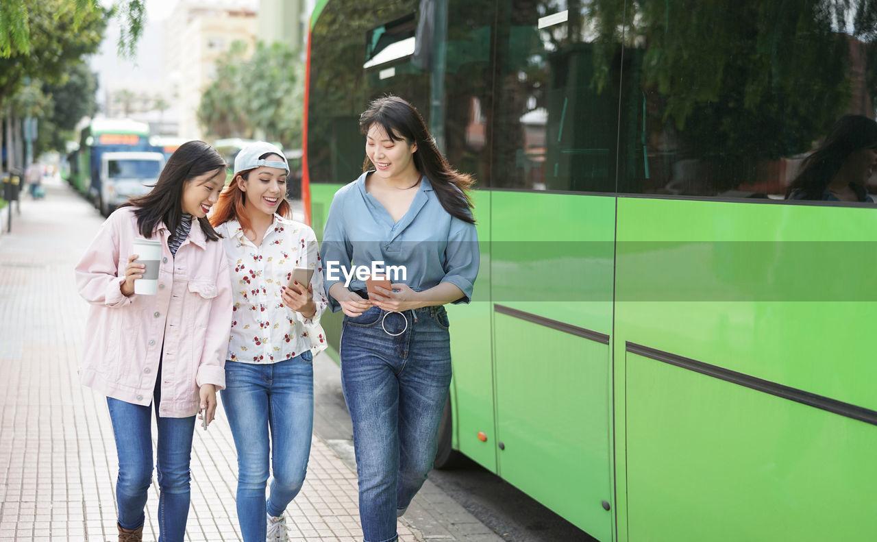 Women using mobile phones in city