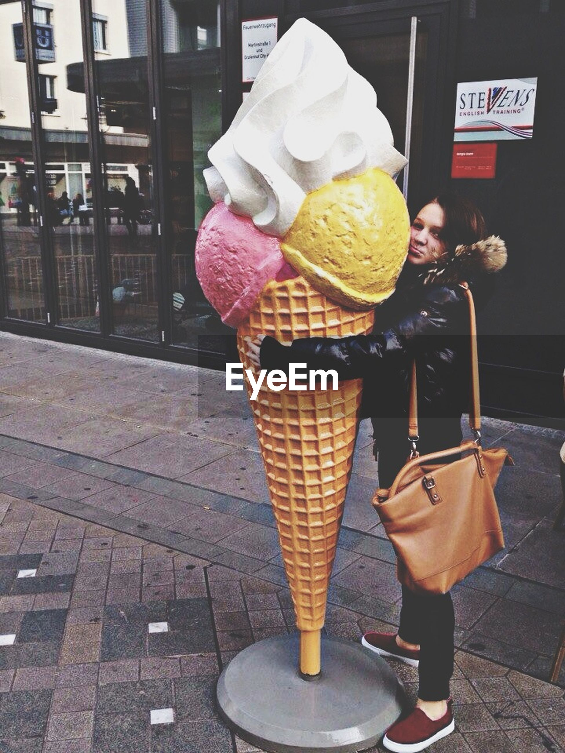 food and drink, holding, food, sweet food, freshness, person, lifestyles, street, men, unhealthy eating, dessert, ice cream, frozen food, incidental people, table, casual clothing, leisure activity, indoors