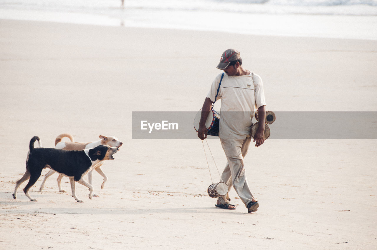 FULL LENGTH OF MAN WALKING WITH DOG ON SAND